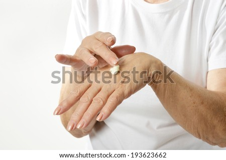 Older woman applying cream on hands closeup on white background - stock photo