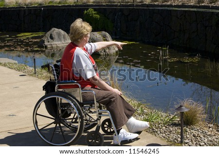 Older woman in a wheel chair at the park - stock photo