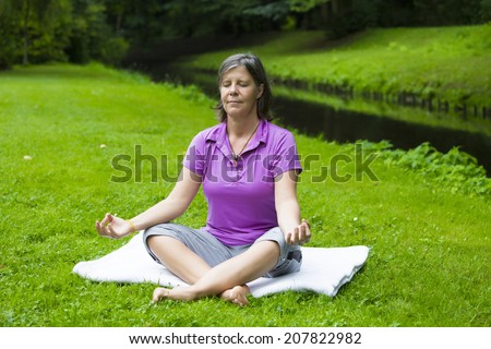 older woman in park by a river doing yoga - stock photo