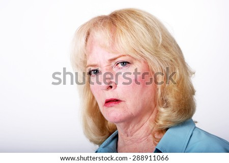 Older woman looking at the camera with a stern expression.  Image is isolated against white with ample copy space. - stock photo