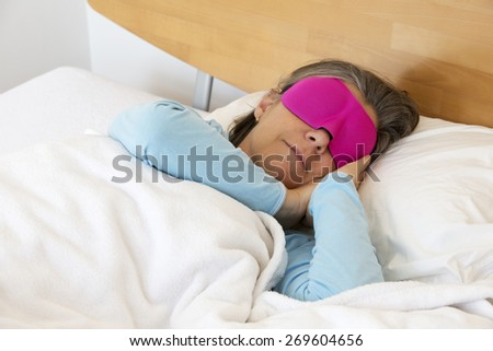 older woman lying in bed and sleeping peacefully with a sleep mask on - stock photo