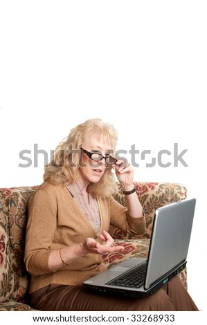 older woman studying finances on a laptop computer - stock photo