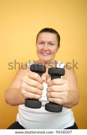 Older woman working out with weights; focus on the hands with weights - stock photo