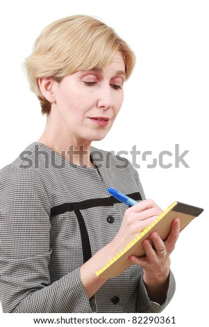Older woman writing on a small notepad - stock photo