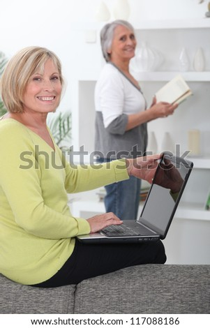Older women with computer and book - stock photo