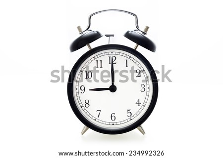 Oldfashioned black glossy alarm clock showing 9 o'clock