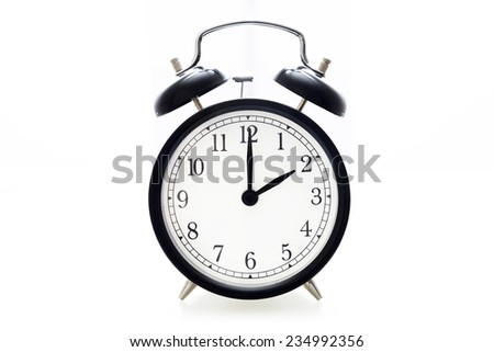 Oldfashioned black glossy alarm clock showing 2 o'clock