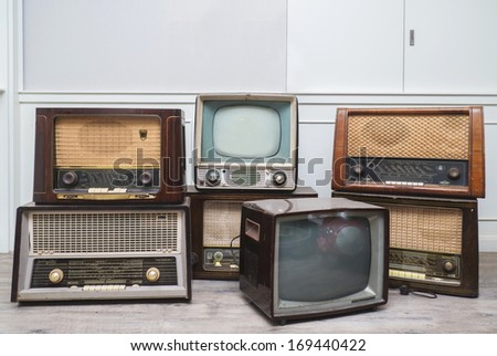 oldie things. radios, tvs, camera, and frame on wooden floor - stock photo