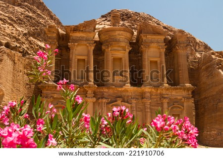 Oleander bush and the facade of the Monastery, one of the famous monuments of the ancient Nabatean city of Petra, Jordan. - stock photo