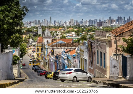OLINDA, BRAZIL - MARCH 17, 2014: Architecture of Olinda's historic buildings in the foreground contrasts with the modern Recife's skyscrapers in the background on March 17, 2014 in Pernambuco, Brazil. - stock photo