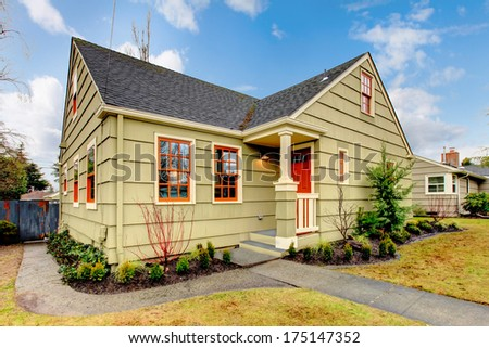 Olive house with red front door and orange window treatment. - stock photo