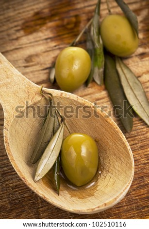 olive in spoon on a wooden table - stock photo