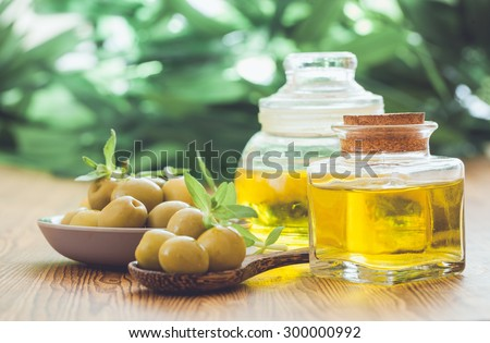 Olive oil and olive  on the wooden table - stock photo