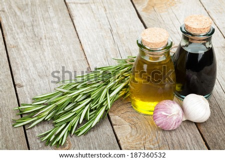 Olive oil and vinegar bottles with spices over wooden table background - stock photo
