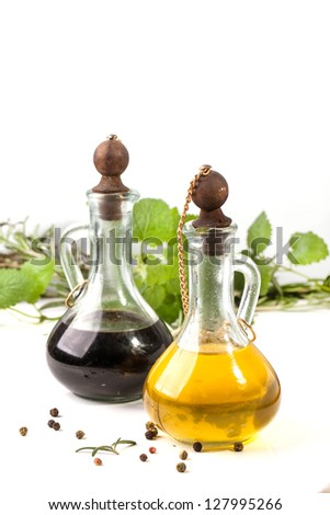 Olive oil and vinegar in vintage bottles, herbs and pepper over white - stock photo