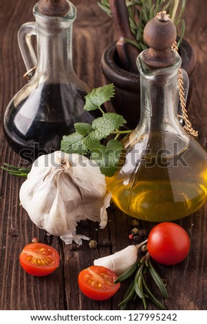 Olive oil and vinegar in vintage bottles on wooden table, sliced tomatoes cherry with garlic, mint and rosemary in wooden mortar - stock photo
