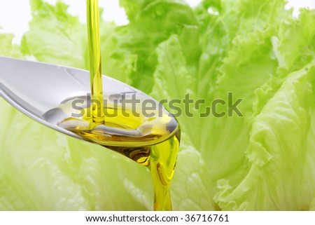 olive oil being pouring in a spoon - stock photo