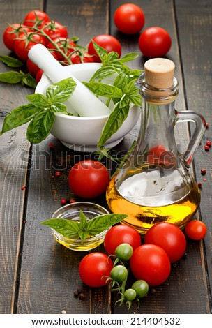 Olive oil bottle, cherry tomatoes and fresh basil - stock photo