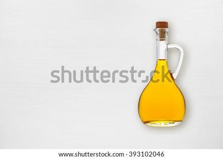 Olive oil bottle on white wooden table - stock photo