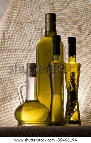 Olive oil bottle still-life over  textured background with back light - stock photo