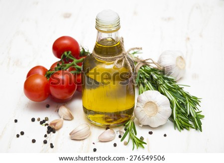 Olive oil, cherry tomatoes, garlic and rosemary on a white wooden background - stock photo