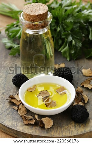 Olive oil flavored with black truffle on a wooden table - stock photo