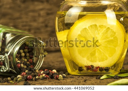 Olive oil flavored with lemon and  peppercorns in  glass bottle on old wooden background - stock photo