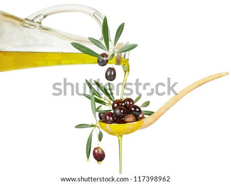 olive oil flows from a bottle in a wooden spoon with branches of an olive tree. Isolated over white background. - stock photo
