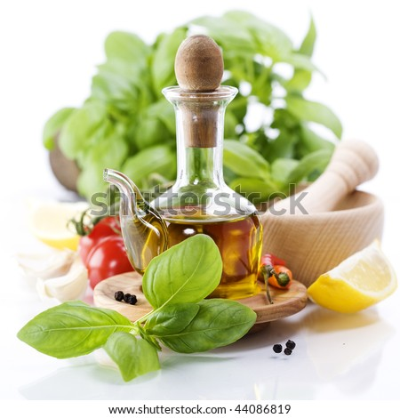 Olive oil, herbs and vegetables over white - stock photo
