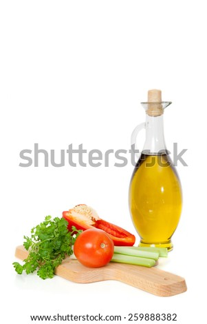 olive oil in a glass jar and fresh vegetables on the Board - stock photo