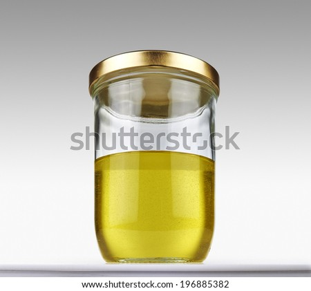 Olive oil into closed glass jar on a grey gradient background - clipping path - stock photo