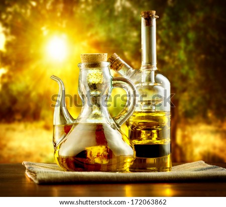 Olive Oil on the Table in garden of Olive Trees. Sun. Healthy eating concept. Mediterranean cuisine. Homemade healthy Olive Oil in Olive Farm - stock photo