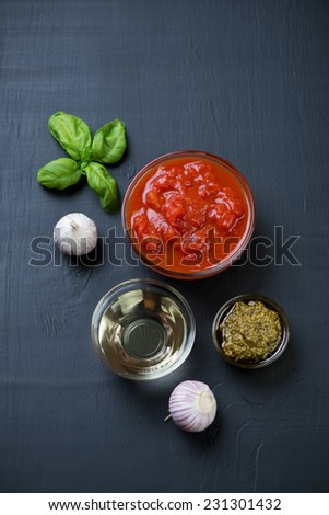 Olive oil, pesto sauce, chopped tomatoes and garlic, above view - stock photo