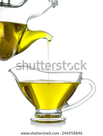 olive oil poured from a jug into a glass - stock photo