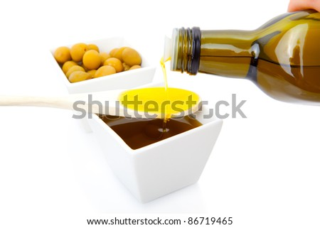 Olive oil poured from an original bottle into a wooden spoon - stock photo