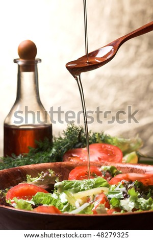 Olive oil poured over salad - stock photo