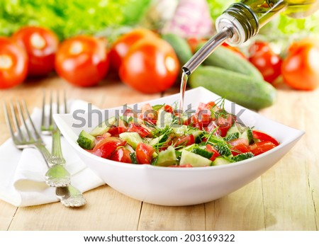 olive oil pouring  into bowl of vegetable salad - stock photo