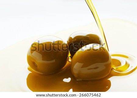 Olive oil pouring on olive fruits on white background - stock photo