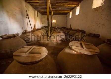 Olive oil storage cellar with Dark brown old historic ceramic pots in Greece - stock photo