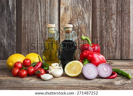 Olive oil, vinegar, organic vegetables and fruits on wooden background. Food ingredients - stock photo