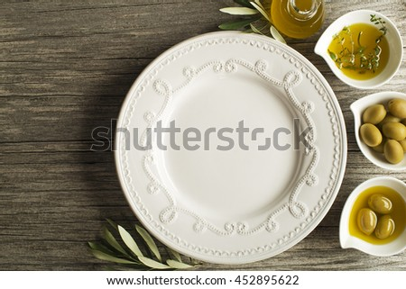 Olive oil with fresh herbs on wooden background - stock photo