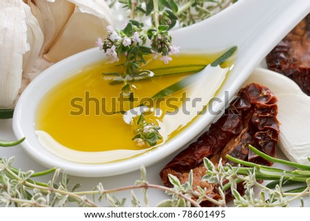 Olive oil with fresh rosemary, thyme, dried tomatoes and garlic. - stock photo