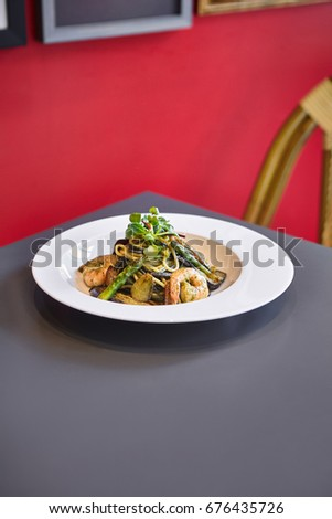 Olive pasta placed at the dining table of the modern interior. Serve with shrimp and asparagus basil.