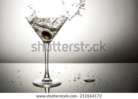 Olive splashing on a martini cocktail - stock photo