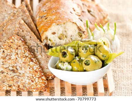 olives and garlic with tasty Italian artisan bread and grain bread - stock photo