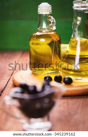 olives and olive oil in bottle, on a wooden background