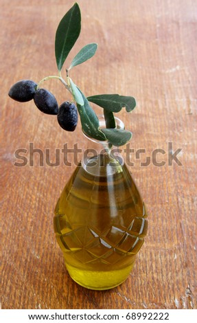 Olives and Olive Oil on a wooden table - stock photo