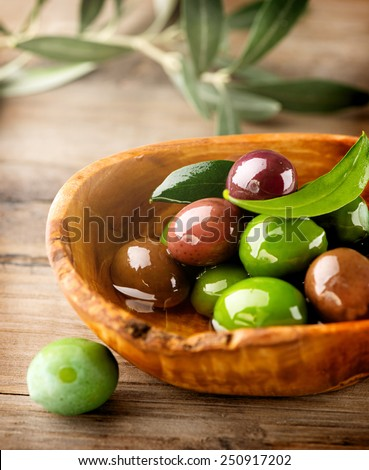 Olives and Olive Oil on the wooden table. Vertical image - stock photo