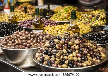 Olives at a market stall. Countertop with different pickling olives on the market.  Green, black and others.(selective focus)