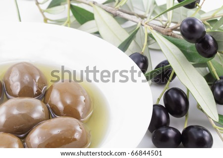 Olives in a bowl and olive tree branch - stock photo